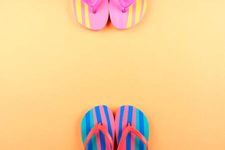 Photo for Colorful neon flip flops on orange summer background. Frame with copy space. - Royalty Free Image