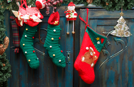 Foto de Christmas decorations: red Santa's boot, green stockings, evergreen branch with pine cones and christmas toys on blue doors of old wardrobe. - Imagen libre de derechos