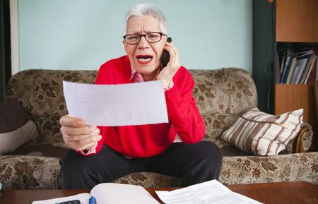 Foto de Senior old woman yelling at her bank, angry with the amount on her bills, arguing with customer service agent - Imagen libre de derechos