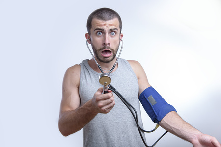 Photo for Young man shocked and surprised by his blood pressure results - Royalty Free Image