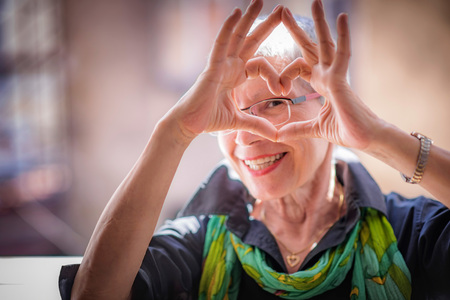 Foto de Cute senior old woman making a heart shape with her hands and fingers - Imagen libre de derechos