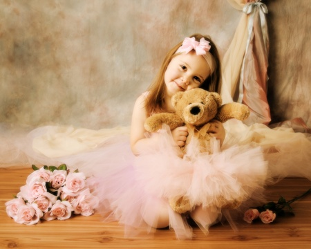 Adorable little girl dressed as a ballerina in a tutu, hugging a teddy bear sitting next to pink roses.