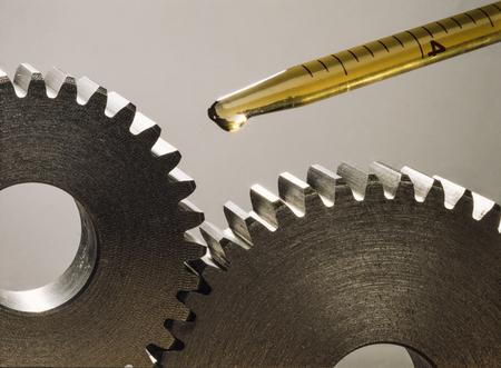 Foto de Lubricating two pinions with a few drops of oil. Mechanical sprockets - Imagen libre de derechos