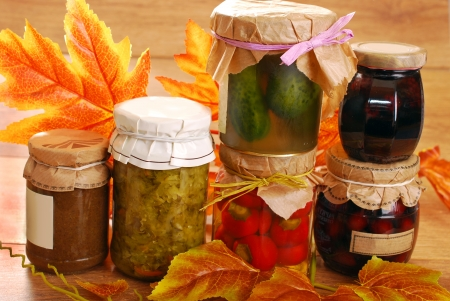 jars of homemade vegetables;fruits and mushrooms preserves in autumn scenery