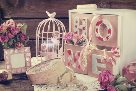 Foto de Vintage home still life with wooden drawers boxpink cage and photo frame in romantic style - Imagen libre de derechos