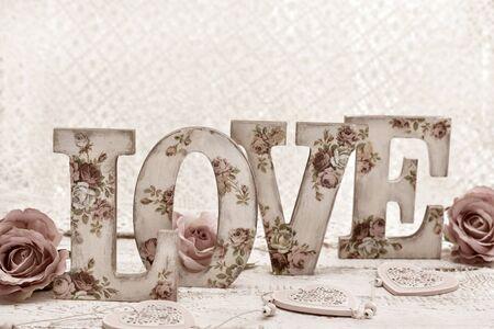 Photo pour vintage style wooden letters LOVE with rose pattern decoupage decoration standing on wooden table - image libre de droit