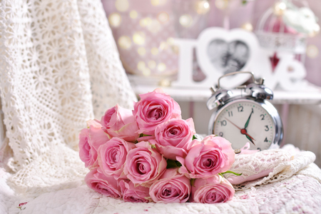 Foto de romantic bunch of pink roses lying on the bed,retro alarm clock and love decoration in shabby chic style interior - Imagen libre de derechos