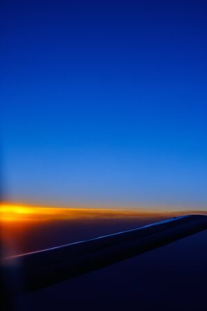Foto de View of the sunset and the wing of the aircraft from the porthole during the flight - Imagen libre de derechos