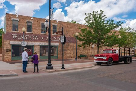 Photo pour winslow Arizona, USA 5/16/2016. Two people standing on the corner. Side of building with art work windows, people hugging, eagle, truck flatbed ford - image libre de droit