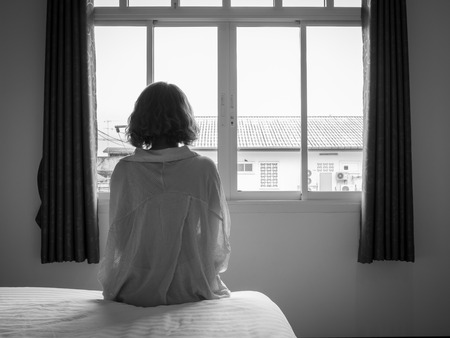 Photo pour Woman short hair sitting on the white bed in hotel room . Lonely woman looking out the window alone in white hotel room, black and white style. - image libre de droit
