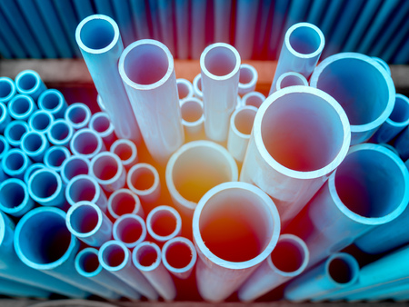 Photo pour Tubes PVC pipes stacked in warehouse. Blue PVC pipes background with sunlight. - image libre de droit