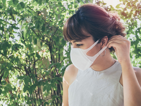 Foto de Beautiful asian woman wearing white protective N95 dust mask on green leaves background with copy space. Protection against pollution concept. - Imagen libre de derechos
