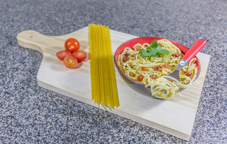 Foto de Noodles in garlic and oil, served in a bowl with bacon and tomatoe - Imagen libre de derechos