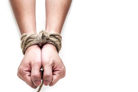 Foto de victim, slave, prosoner male hands tied by big rope isolated on the white background. People have no freedom concept image. - Imagen libre de derechos