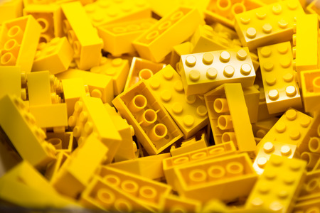 Foto de Pile of Building Blocks with focus and highlight on a selected piece with available light - Imagen libre de derechos