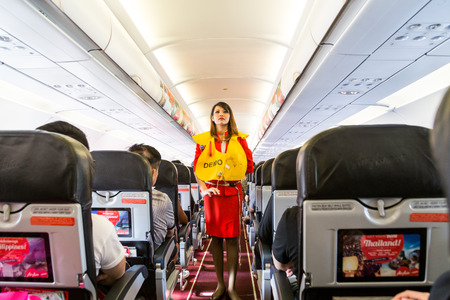 Foto de KUALA LUMPUR, Malaysia, June 8, 2017: Airasia hostess demonstrate safety procedures to passengers prior to flight take off. - Imagen libre de derechos
