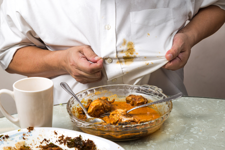 Photo pour Person accidently spilled curry stain onto white shirt and reacted with frustration. - image libre de droit
