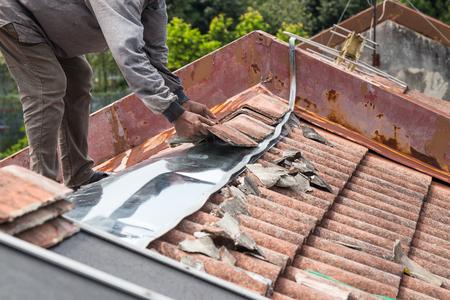 Foto de Asian worker replacing roof tiles and metal sheets of old residential building roof - Imagen libre de derechos