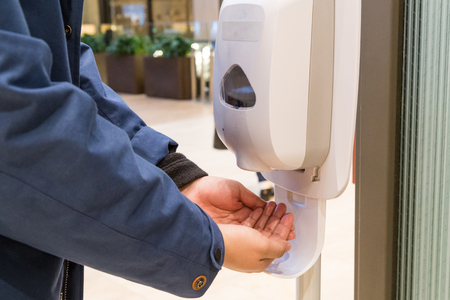 Photo pour Person cleaning hand with anti-bacterial hand disinfectant sanitizer dispenser in public mall in Japan - image libre de droit