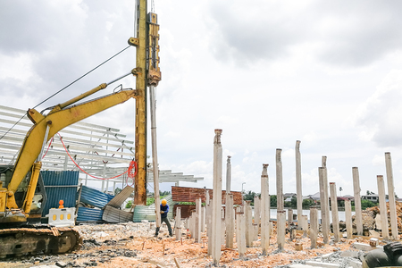 Photo pour Worker carrying out ground piling work at construction site with heavy machinery - image libre de droit