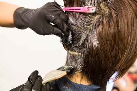 Foto de Closeup of hair dresser applying chemical color dye onto hair of customer in salon - Imagen libre de derechos