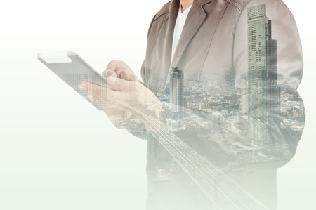 Double exposure of city and Businessman use Tablet device as Business development concept.