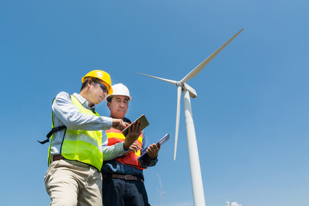 Foto de Alternative Power or Renewable Energy Technology Project Development Concept, Engineer and Architect discuss over Digital Wireless Tablet and Clipboard while working at Wind Turbine Power Generator Tower site. - Imagen libre de derechos