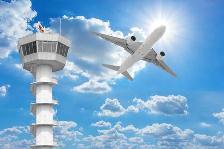 Photo pour Passenger aircraft  flying above air traffic control tower against blue sky - image libre de droit
