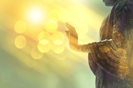 Foto de hand of buddha statue with yellow bokeh background, light of wisdom and concentration concept - Imagen libre de derechos