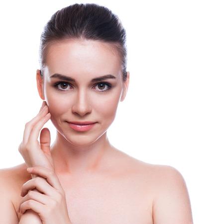 Foto de Beautiful Young Woman Touching Her Face.Fresh Healthy Skin.Isolated on White - Imagen libre de derechos