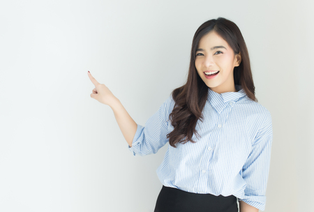 Photo pour Portrait of young asian business woman pointing up over white background. - image libre de droit