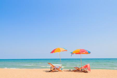 Photo pour Beach chair and umbrella on sand beach - image libre de droit