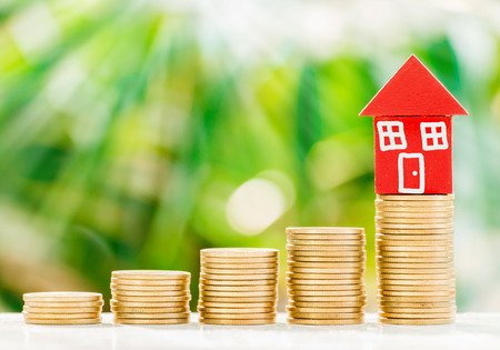 Foto de Red home model put on golden coins with fresh green nature background, saving to buy house concept - Imagen libre de derechos