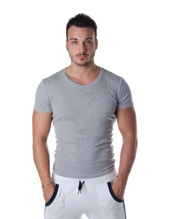 Athletic and handsome young man standing confident with hands in his pockets, isolated on white