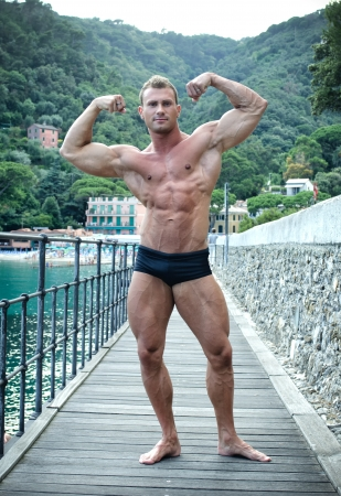 Double biceps pose for young, attractive bodybuilder by the sea showing muscular body