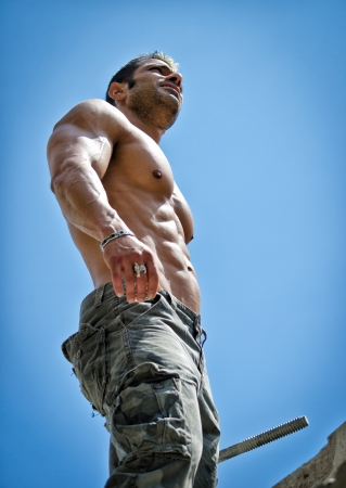 Photo for Hot, shirtless, muscular construction worker shirtless seen from below against blue sky - Royalty Free Image