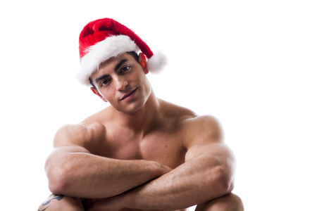 Foto de Attractive young muscle man sitting and smiling with muscular ripped body in Santa Claus's red hat - Imagen libre de derechos