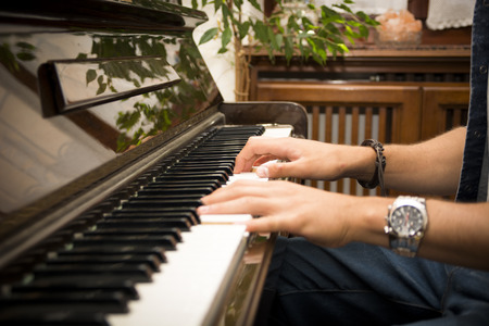 Male hands playing piano indoors inside house