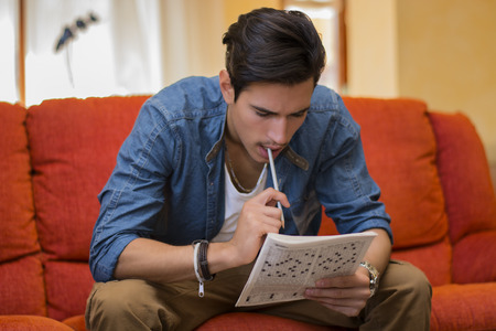 Photo pour Young man sitting doing a crossword puzzle looking thoughtfully at a magazine with his pencil to his mouth as he tries to think of the answer to the clue - image libre de droit