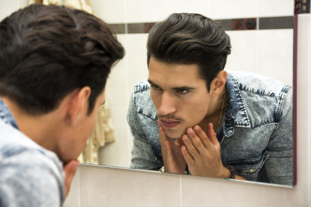 Photo pour Close Up of Young Man Examining Face in Reflection of Mirror and Glaring at Self - image libre de droit
