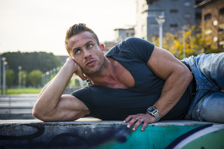 Foto de Handsome muscular blond man lying down in city setting looking to a side - Imagen libre de derechos