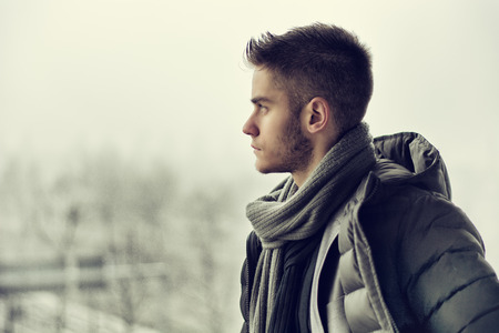 Photo pour Profile view of handsome young man outdoor in winter wearing scarf, looking away thinking - image libre de droit