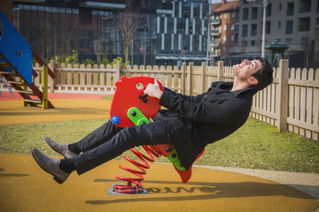 Photo pour Young man reliving his childhood plying in a childrens playground riding on a colorful red spring seat with a happy smile in an urban park - image libre de droit