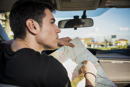 Photo pour Close up Gorgeous Young Man Driving the Car, Holding a Map Asking for Directions While Looking to the Right of the Frame for a Direction. - image libre de droit