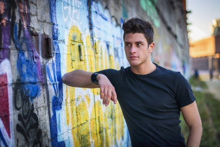 Photo pour Attractive young man standing against colorful graffiti wall, looking away - image libre de droit