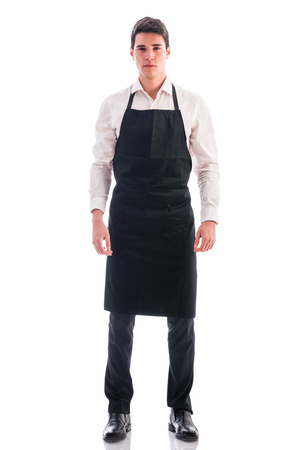 Foto de Full length shot of young chef or waiter posing, wearing black apron and white shirt isolated on white background - Imagen libre de derechos