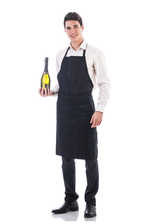 Foto de Attractive young chef or waiter holding green champagne bottle isolated in white - Imagen libre de derechos
