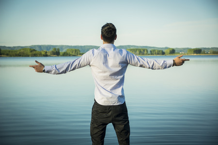 Photo pour Young man in shirt, outdoor with arms spread open enjoying freedom in front of lake, seen from the back. - image libre de droit