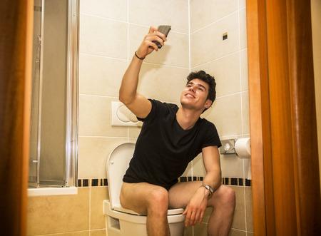 Foto de Smiling young man taking selfie with cell phone while defecating in his bathroom - Imagen libre de derechos