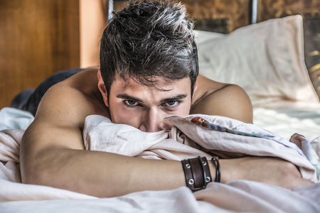 Photo pour Shirtless sexy male model lying alone on his bed in his bedroom, looking at camera with a seductive attitude - image libre de droit